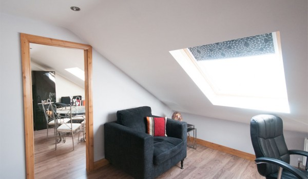 loft conversion, mirror and black chair positioned in open plan room with sky liner windows