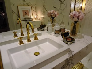 A picture of a sink unit with large gold mirror in an en-suite, one of many great design ideas for a loft conversion
